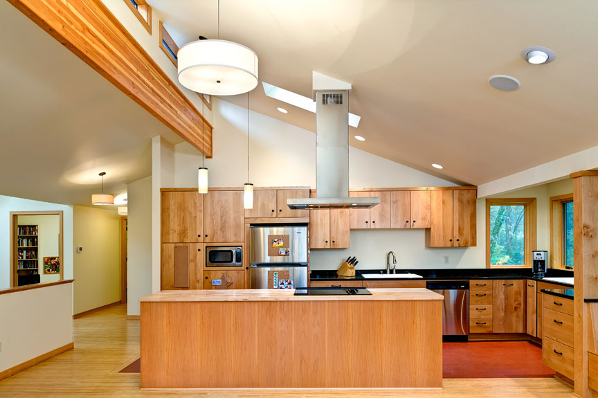 Solid wood cabinets are highlighted by the skylight in this functional kitchen