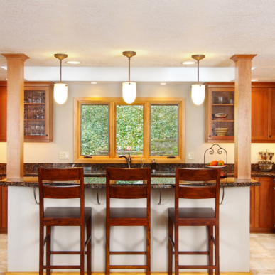 Rich cabinets and dark counters are illuminated by the natural light in this kitchen