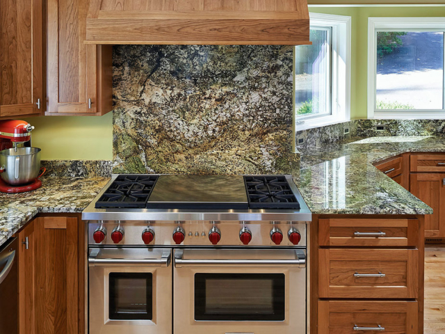 Kitchen with oversized cooktop and oven, marble countertops and backsplash, remodeled by W.L. Construction in Corvallis, Oregon.